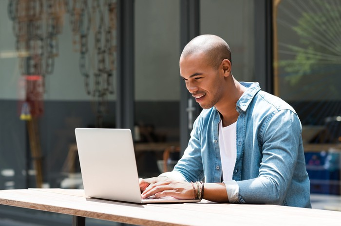 Young male adult typing on a laptop.