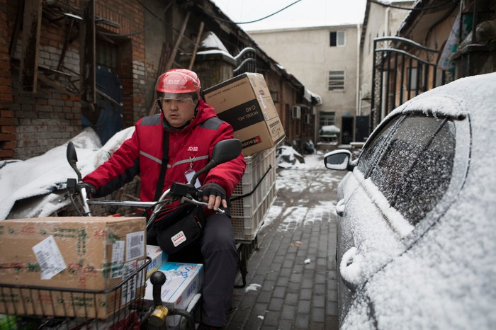 A JD.com delivery man on a motor bike on a snowy street.