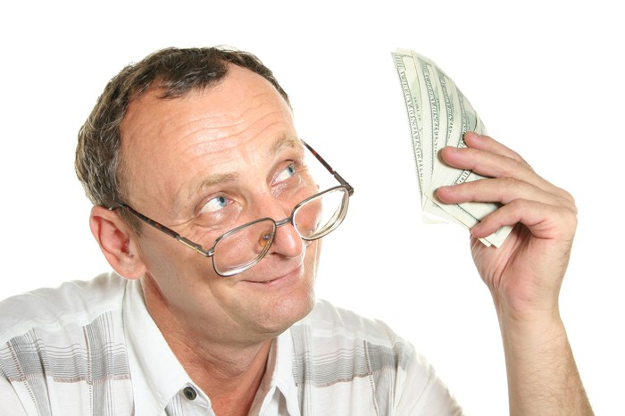 A mature man with glasses looking up and smiling at a pile of cash being held in his left hand.