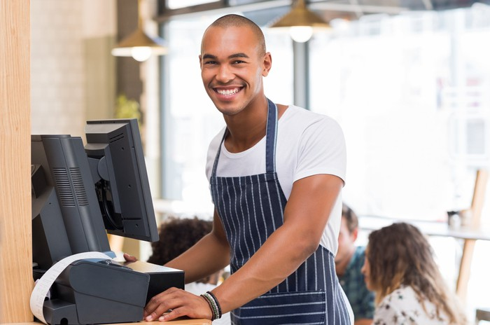 A smiling waiter entering orders at a point-of-sale register.