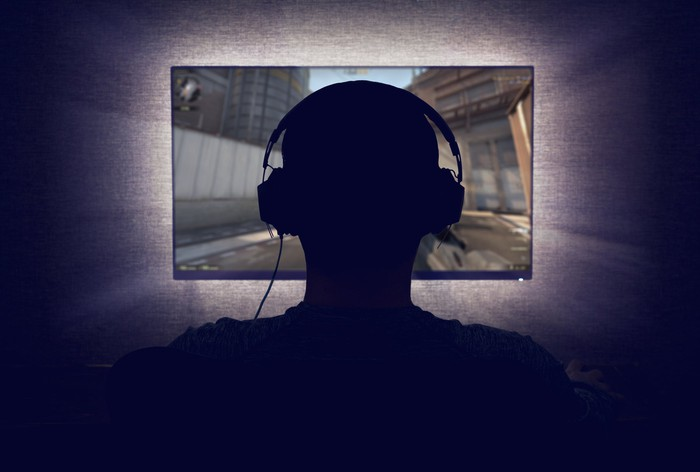 Person playing video game in a darkened room.