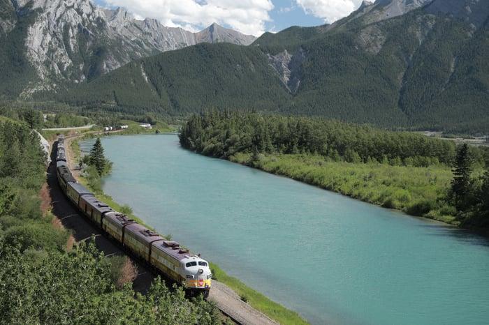 Locomotive moving along tracks next to a river.