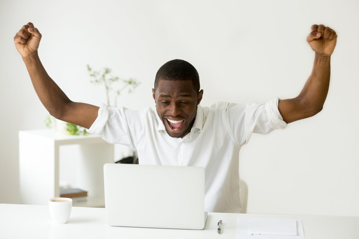 A man looking at a computer raises his arms in triumph.