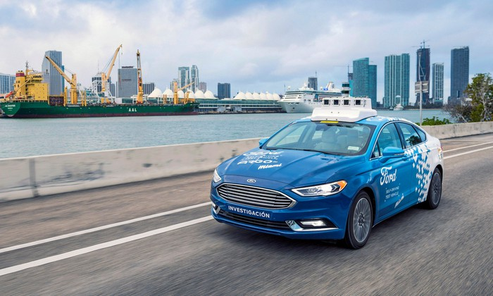 A blue and white Ford Fusion sedan with visible self-driving hardware on a street in Miami, Florida.