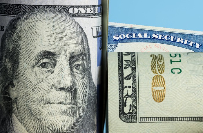 A rolled-up hundred-dollar bill and twenty-dollar bill partially obscuring a Social Security card.