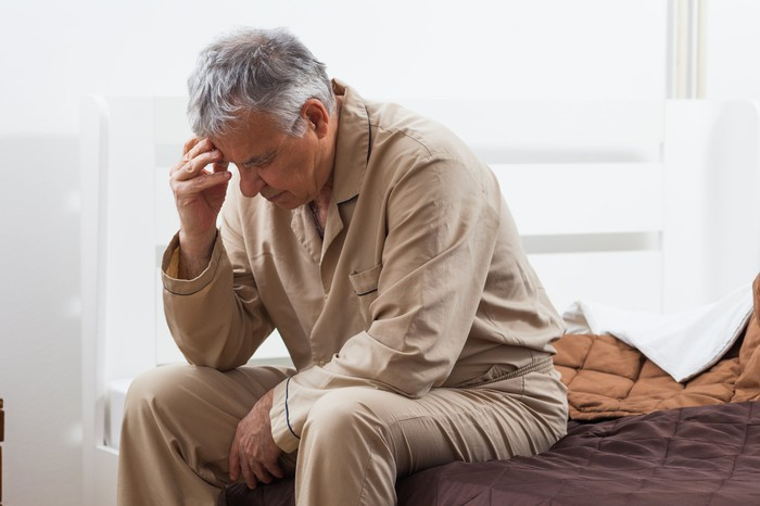 Senior man sitting on a bed while holding his head.