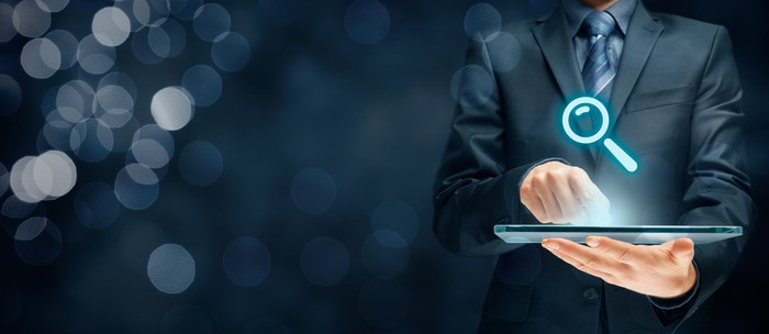 Businessman holding futuristic tablet with head-up display and symbol of a magnifying glass.