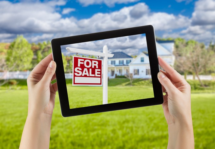 "Female hands holding computer tablet with ""home for sale"" sign on screen, house behind."