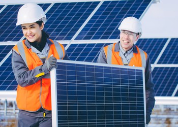 18_09_20 Two people carrying a solar panel at a solar farm_GettyImages-927287372