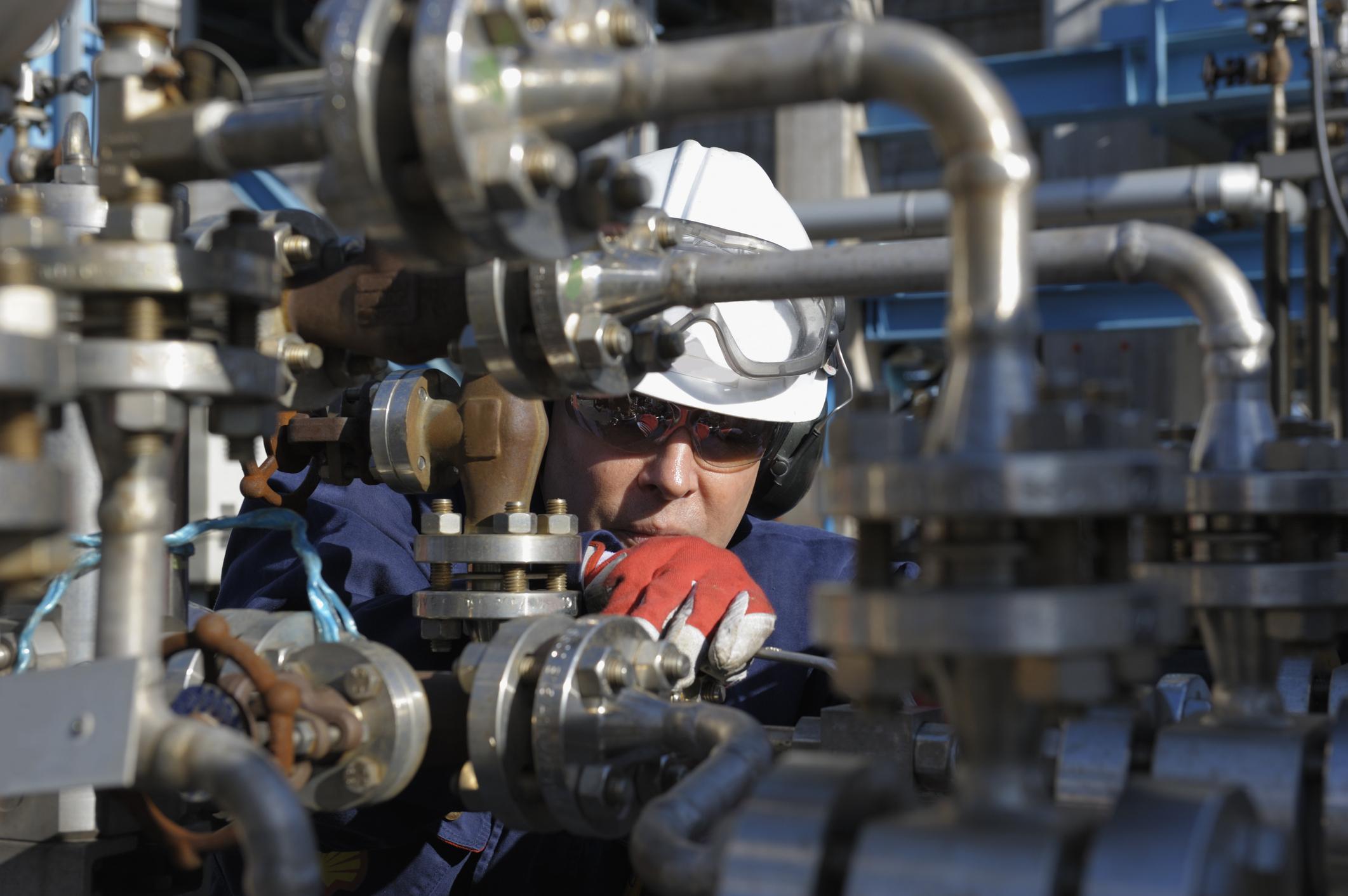 Oil worker inspecting valves.