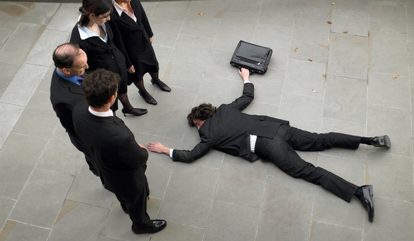 business-people-looking-at-fallen-colleague-getty