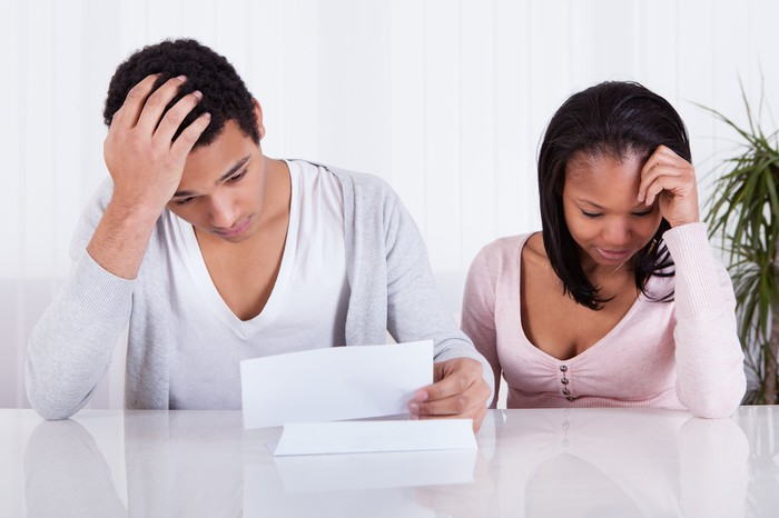 A couple looking worried with head in hands while looking at papers.