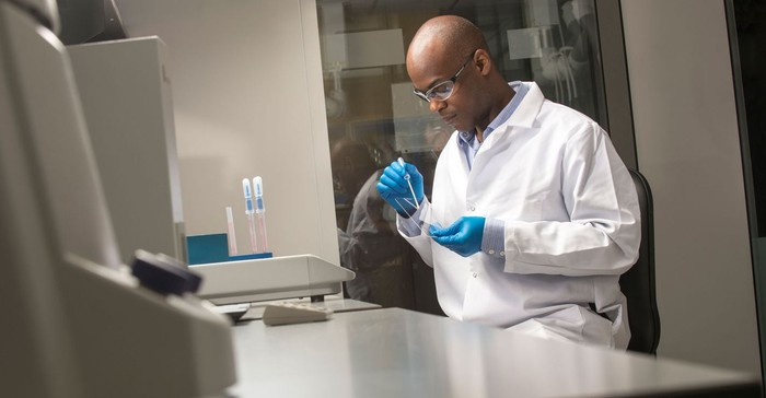Scientist in white lab coat with blue gloves working on Corning glass products.
