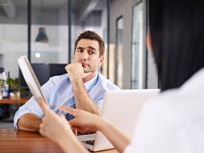 a skeptical male interviewer raises an eyebrow at an interviewer who points at a resume.