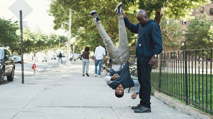 A scene from Netflix and Marvel's Luke Cage that shows one man holding another upside-down.