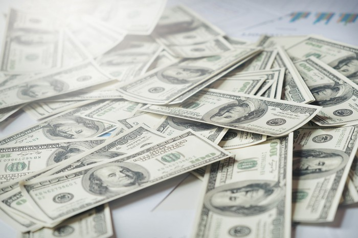 $100 bills lying loosely on a flat surface.