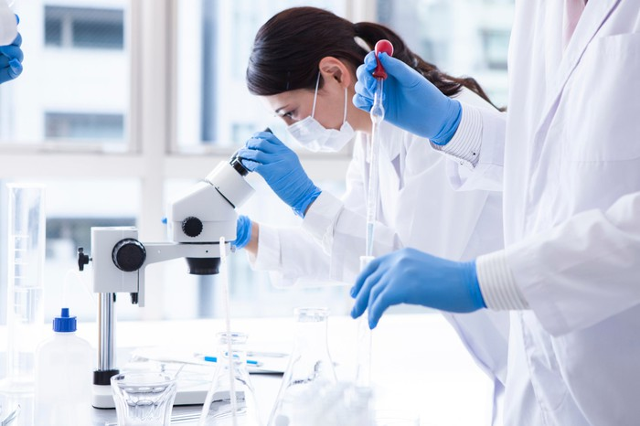 Female scientist in white lab coat looking through microscope with another scientist holding a dropper.