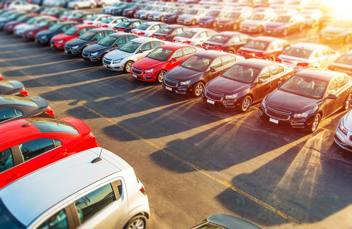Multiple rows of cars at an automotive dealership.