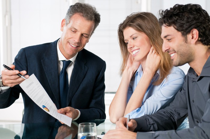 Man in suit presenting document to smiling young couple.