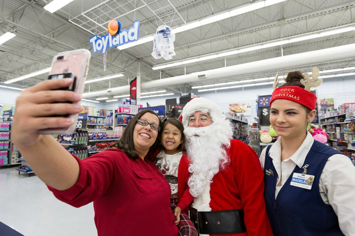 Walmart workers and a child take a picture with Santa Claus.