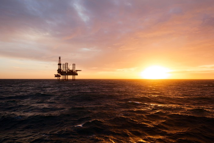 A silhouette of an offshore drilling rig at sunset.