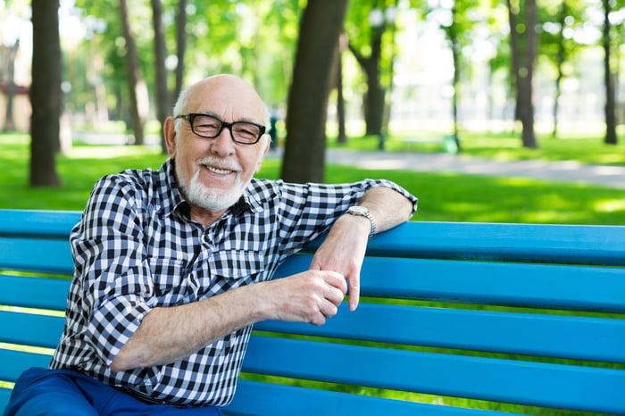 Smiling senior man sitting on blue bench outdoors.