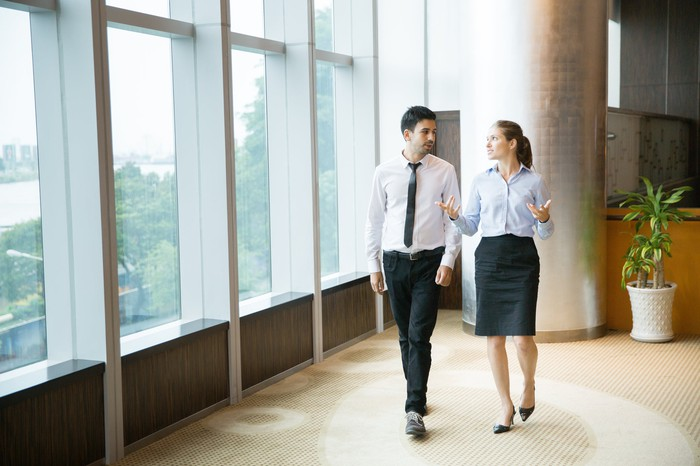 Professionally dressed man and professionally dressed woman talking and walking