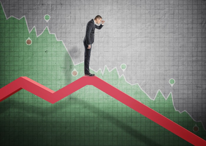 Man looking downward as he stands on a downard-pointing red arrow with a graph in background.