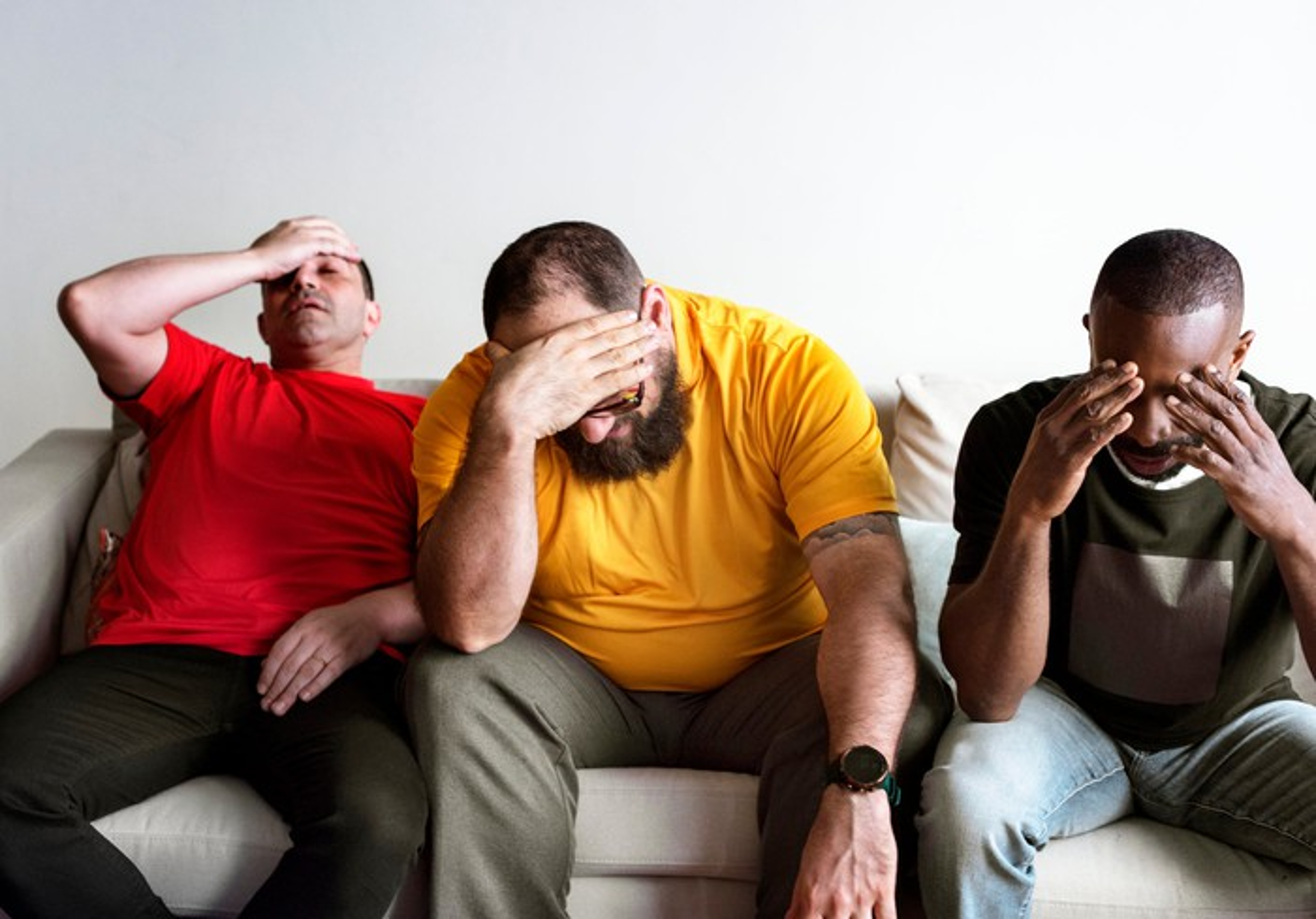 Three distressed looking people on a sofa.