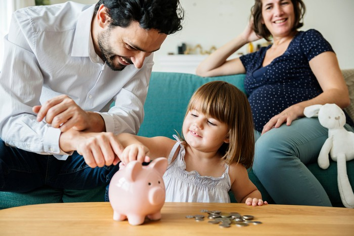 Young girl inserts coin into piggy bank while her father and pregnant mother look on.