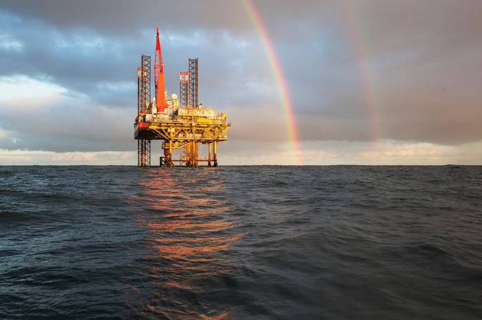 An offshore drilling rig with a rainbow behind it.