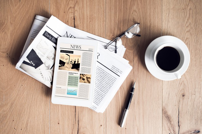 A newspaper on a table next to a cup of coffee.