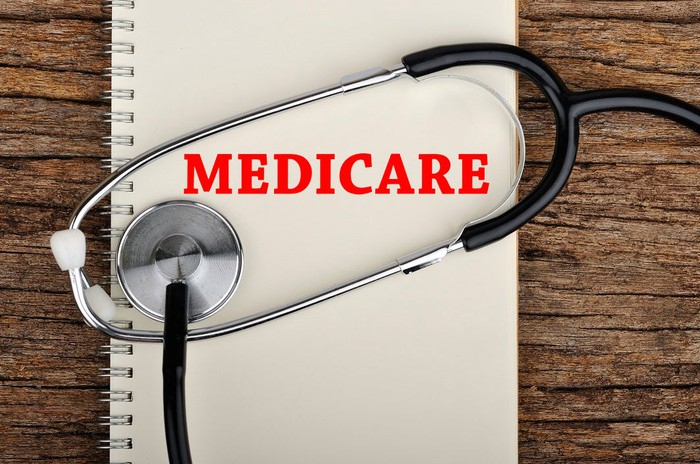 Notebook on desk with Medicare printed in red, and stethoscope on top.