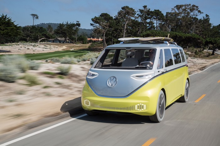 The VW I.D. Buzz concept, an electric minivan with styling that recalls VW's iconic 1960s Mircrobus, is shown driving on a beach road in California, with two surfboards on its roof rack.