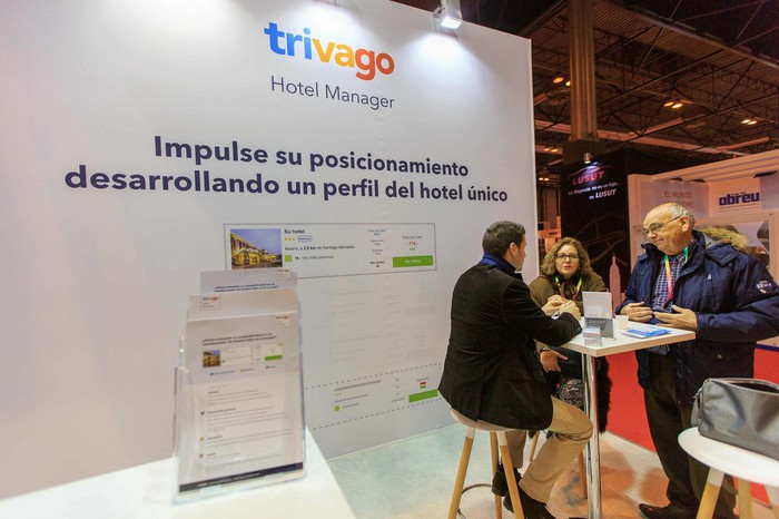 Conference booth with Trivago logo and description of Hotel Manager product, with three people talking at a table.
