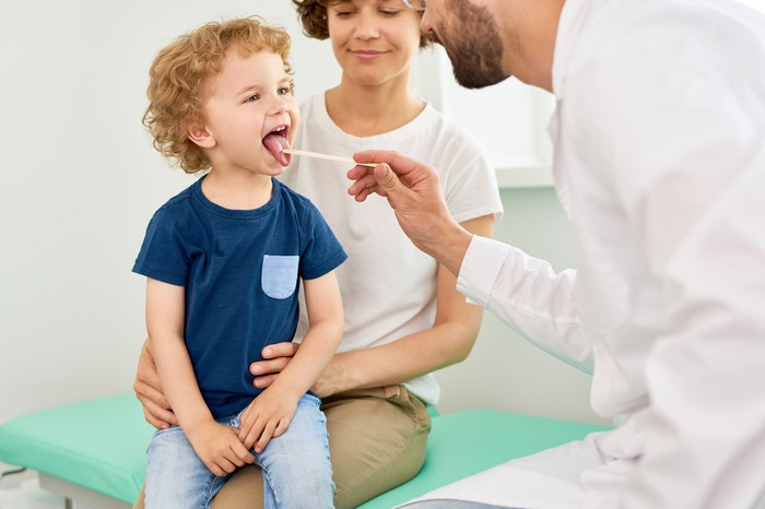Woman holds boy on lap while doctor uses tongue depressor on him.
