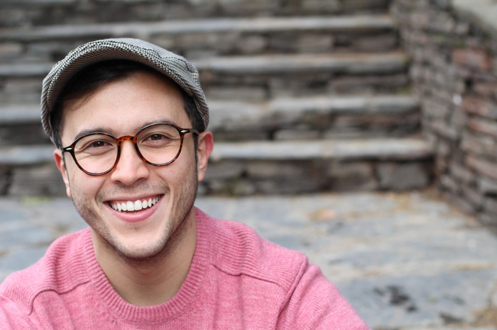 Smiling man in glasses and hat.