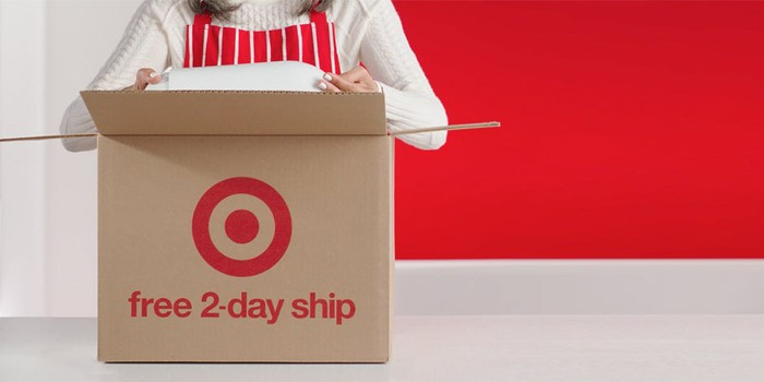 A person putting an item in a box with the target logo and free 2-day ship printed on it.
