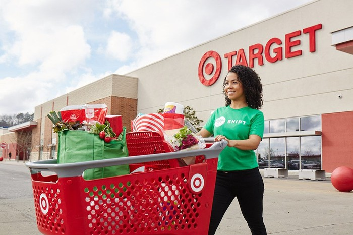 A woman in a Shipt T-shirt pushes a loaded Target shopping cart.