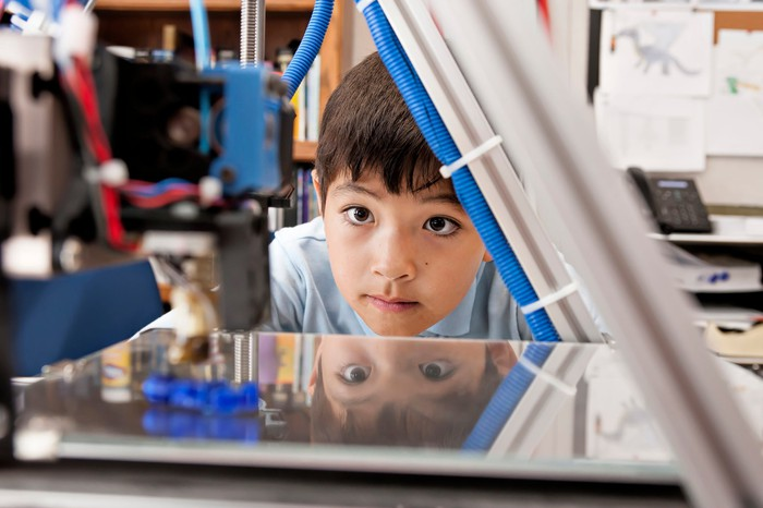 Child watching a 3D printer at work