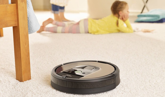 Round robotic vacuum cleaner on a white carpet near a chair, with a child lying on the floor nearby.