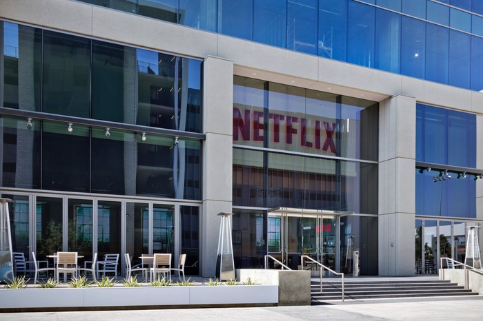 Netflix's Hollywood offices feature lots of windows and a front patio with tables and chairs.