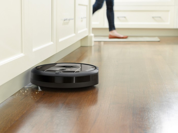 Roomba picking up crumbs from a hardwood floor using its side-sweeping brush