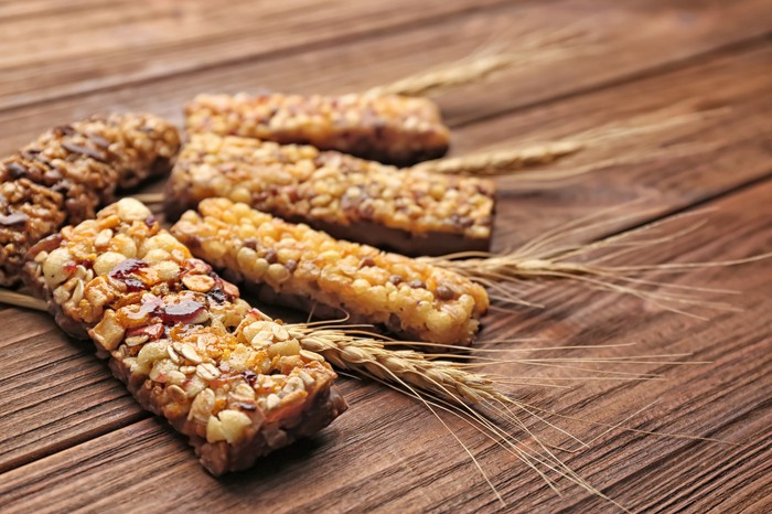 Cereal snack bars and stalks of wheat on a wooden table