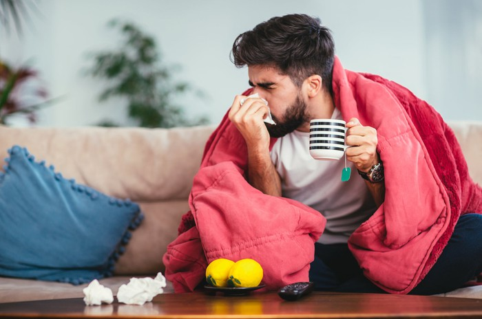 A man wrapped in a blanket and holding a mug of tea blows his nose into a tissue.