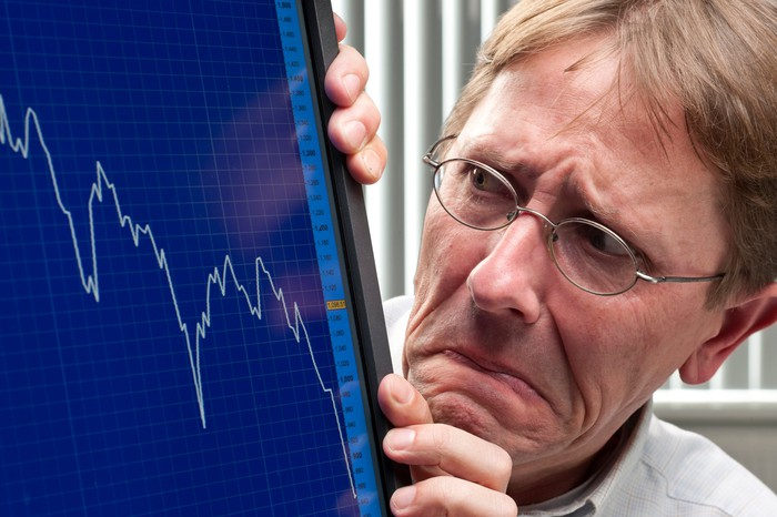A visibly worried investor cowering as he looks at a plunging chart on his computer monitor.