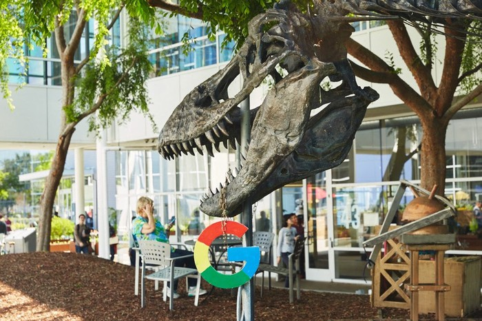 "Dinosar skeleton at the Googleplex headquarters with a ""G"" logo hanging from its jaws"