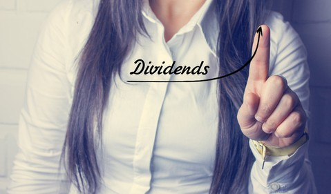 18_08_21 Woman using her finger to show up trend and word dividend_GettyImages-887440046