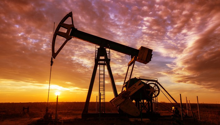 An oil pump with a dramatic sunset in the background.