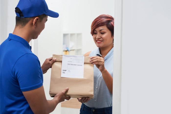 Delivery person handing over a food package to a customer.